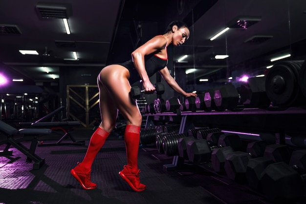 Attractive fit sexy woman in the gym crouches with a barbell. woman training back.