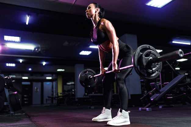Attractive fit sexy woman in the gym crouches with a barbell. woman training back