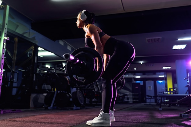 Attractive fit sexy woman in wireless headphones listen music and doing crouches with a barbell in the gym. woman training back