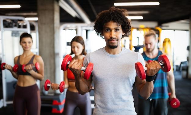 매력적인 맞는 스포츠 사람들이 체육관에서 운동하고 있습니다