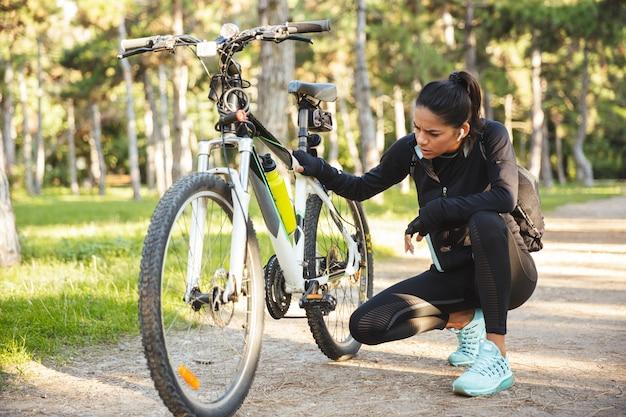 Привлекательная спортивная спортсменка, ремонтирующая велосипед в парке, слушает музыку в беспроводных наушниках