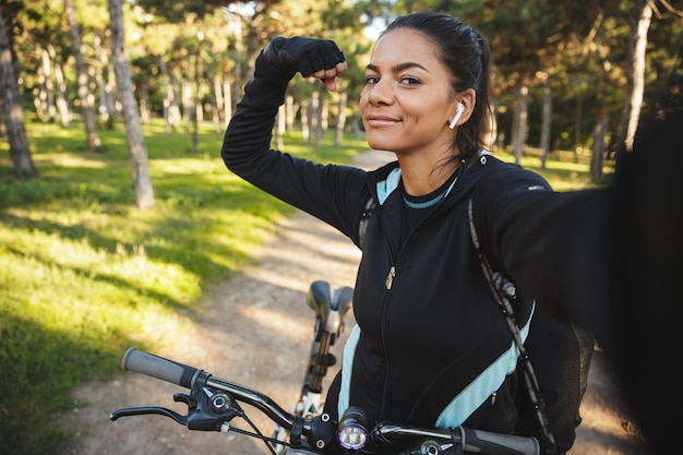 Привлекательная спортивная женщина катается на велосипеде в парке, слушает музыку в беспроводных наушниках, делает селфи