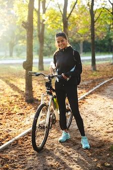 公園で自転車を持ち、ボトルから水を飲む魅力的なフィットスポーツウーマン