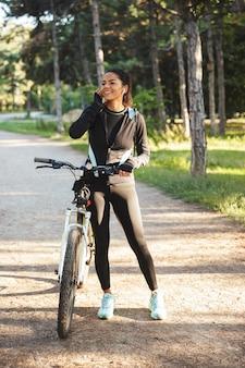 公園で自転車を持ち、ワイヤレスイヤホンで音楽を聴く魅力的なフィットスポーツウーマン