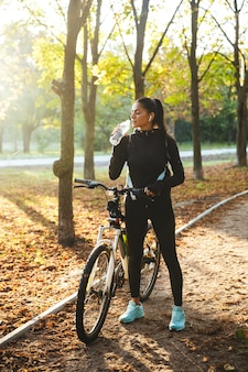 Attractive fit sportswoman with a bicycle at the park, drinking water from a bottle