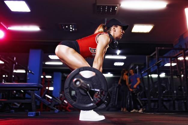 Attractive fit woman in cap and headphones listening music and doing crouches with a barbell in the gym. woman training back