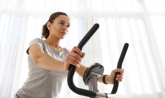 Привлекательная подтянутая женщина тренируется на велотренажере дома в прекрасный солнечный день