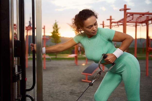 ジムのマシンで筋肉を曲げる魅力的なフィットの女性。アウトドアジムでエクササイズマシンケーブルクロスオーバーで運動する美しい女性アスリート。