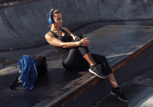 스포츠웨어에 매력적인 맞는 여자는 스포츠 공원에 앉아있는 동안 헤드폰으로 음악을 듣는