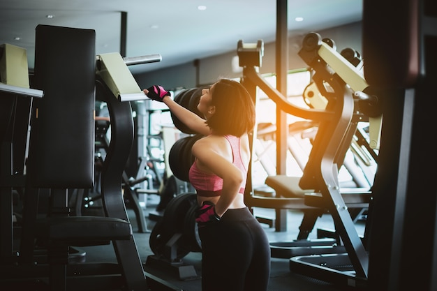 Attractive fit woman relaxing after workout in gym fitness