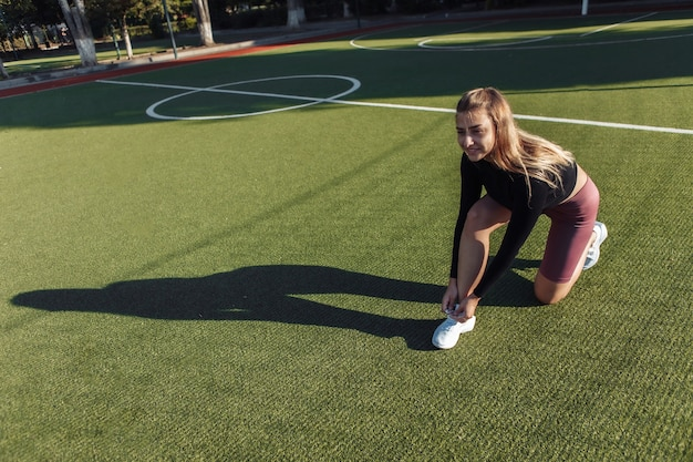 スタジアムで靴紐を結ぶ魅力的なフィットの女性。