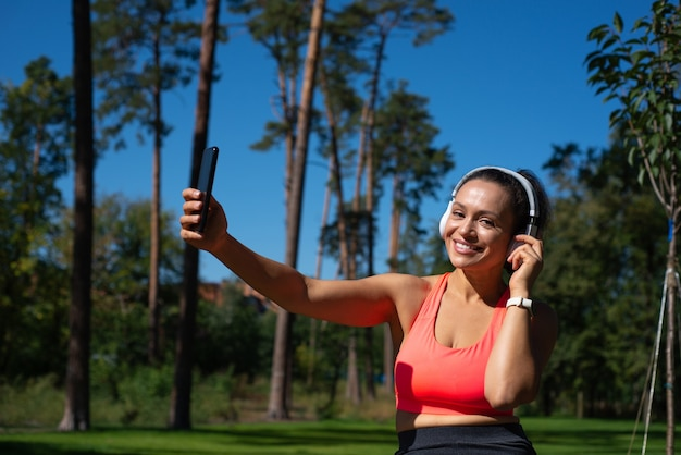 Attractive fit woman with headphones and mobile phone on her hand smiles at the camera while having relax on the background of pine forest