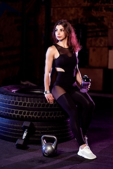 Attractive fit woman with shaker posing on big tire in the gym