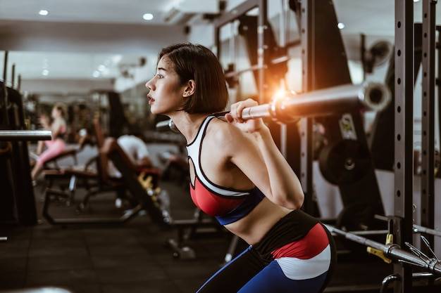 Attractive fit woman workout with barbell in gym fitness