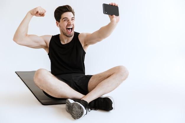 Привлекательный молодой спортсмен сидит на коврике для фитнеса с мобильным телефоном, делает изолированное селфи и разгибает мышцы