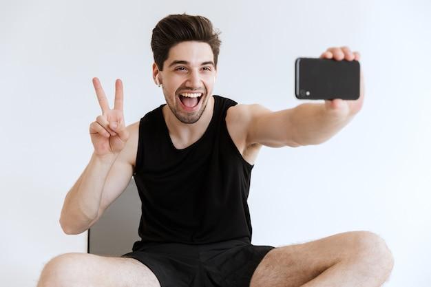 Привлекательный молодой спортсмен сидит на фитнес-коврике с мобильным телефоном и делает изолированное селфи