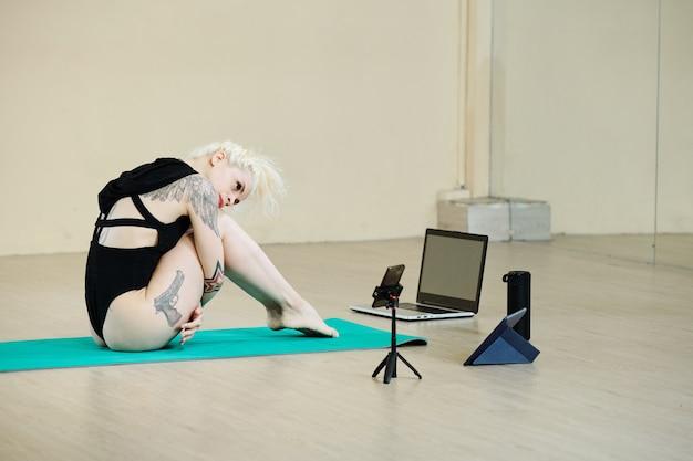 Привлекательная подтянутая молодая женщина снимает танцевальное видео на смартфоне в классе
