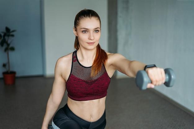 スポーツウェアの魅力的なフィットの若い女性は、ロフトスタジオでダンベルと笑顔の女の子の列車を着用します