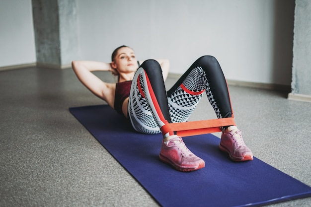 Attractive fit young woman sport wear fitness girl model doing stretching with elastic band doing sit-ups loft studio workout class