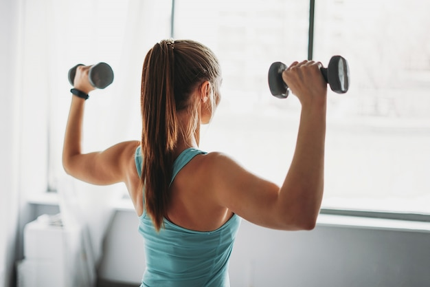 Attractive fit young woman in sport wear fitness model girl trains with dumbbells studio workout classes
