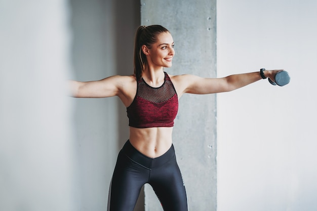 Attractive fit young woman in sport wear smiling girl trains with dumbbells at the loft studio