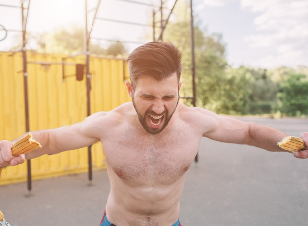 屋外の演習を行う魅力的なフィットネス男。スポーツ、クロスフィット。屋外でのトレーニング。筋肉男の屋外トレーニング。