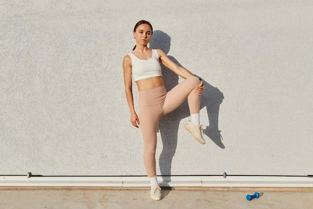 白いスポーツトップとベージュのレギンスを身に着けている灰色の壁の近くでポーズをとる魅力的なフィットネスモデルの女の子