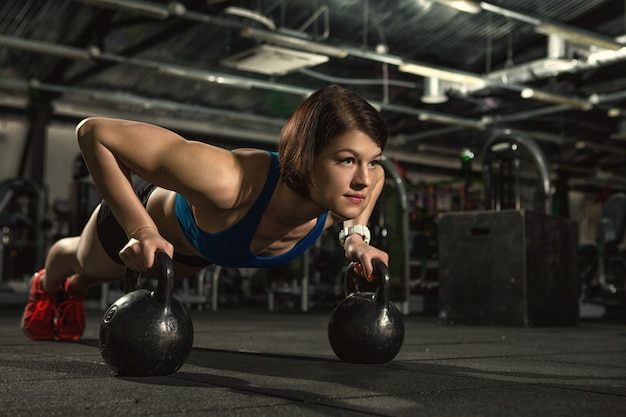 Attractive fitness woman doing pushups with on weights