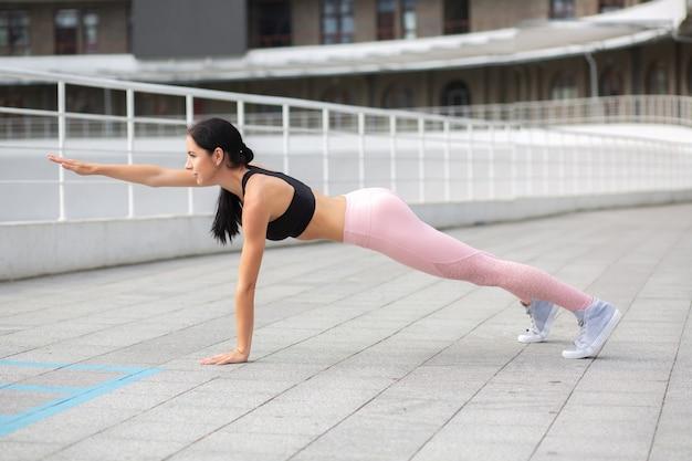 魅力的なフィットネスの女性は遊び場で板張りのスポーツ服を着ています