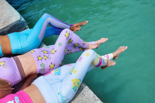 Attractive fitness women wearing modern clothes lying on the pier near sea. muscular abdomens and legs close-up. sports wear style