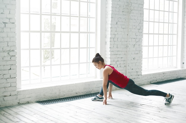 Attractive flexible young female in sportswear warming up legs before front split. brunette girl stretching muscles after cardio workout, standing in low lunge exercise or anjaneyasana by large window