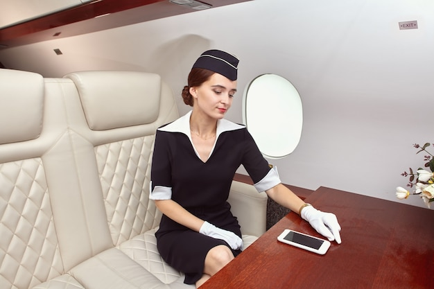 Attractive flight attendant is sitting in business class of airplane and looking at screen of smartphone near porthole.