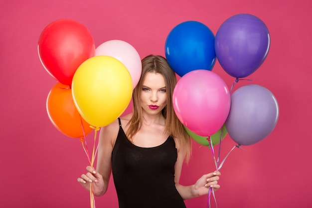 Привлекательная кокетливая сосредоточенная молодая женщина с разноцветными воздушными шарами думает и планирует сюрприз
