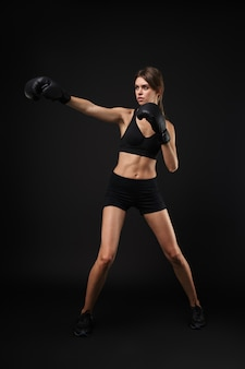 黒の背景、ボクシングの練習で隔離のスポーツブラとショートパンツを身に着けている魅力的な集中若い健康的なフィットネス女性
