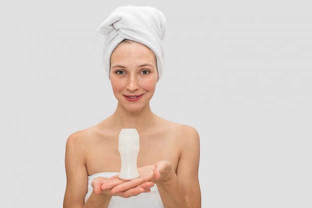 Attractive and freckled woman poses. she holds deodorant with both hands. she smiles. there are white towel around her hair.