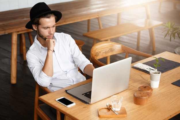 Attractive freelancer dressed in white shirt working remotely sitting at wooden table in front of open laptop computer and looking at screen with thoughtful confident expression, leaning on his elbow