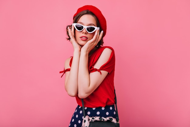 Attractive french girl with pale skin posing. indoor photo of lovable young lady in sunglasses standing.