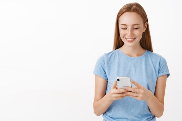 Привлекательная дружелюбная и веселая рыжая женщина с веснушками, улыбающаяся и использующая смартфон, глядя на экран устройства, развлекается