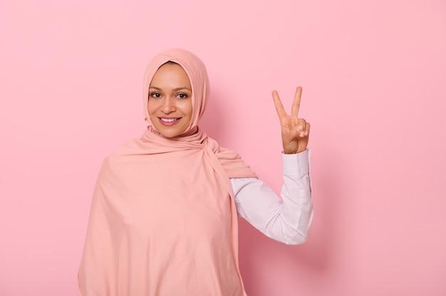 魅力的なフレンドリーなアラブのイスラム教徒の女性の色のヒジャーブは、指の平和のサインを示し、カメラを見て歯を見せる笑顔で笑って、コピースペースでピンクの背景に分離