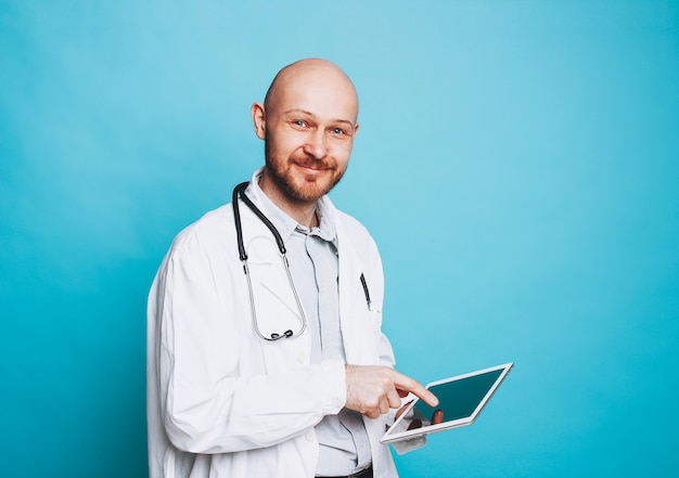 Привлекательный дружелюбный лысый бородатый улыбающийся доктор с планшетом, глядя на камеру, изолированных на синем фоне