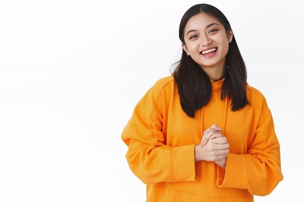 Привлекательная дружелюбная азиатская девушка в модной оранжевой толстовке с капюшоном, держится за руки у груди и вежливо улыбается, объясняет командное задание, работает на полставки репетитором, белая стена