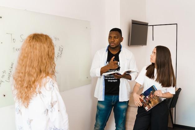 魅力的なフレンドリーな同僚がオフィスで一緒に働いて、白い部屋で何かについて話し合っています