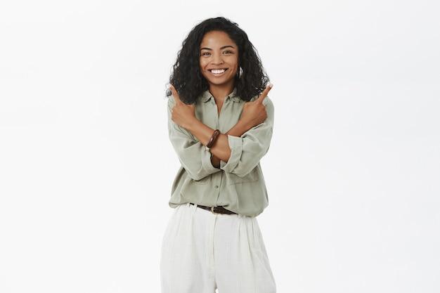 ブラウスとパンツの魅力的なフレンドリーな外観の創造的な浅黒い肌の女性は、さまざまな側面を指している体の上に腕を交差させます