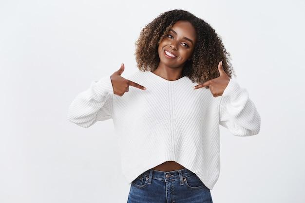 魅力的なフレンドリーな見た目のかわいいアフリカ系アメリカ人女性アフロ、人差し指の中心を傾ける頭を傾けて自信を持って宣伝する製品を笑顔、ボランティア、自分自身を提案する