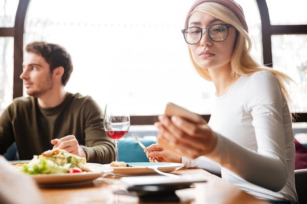 カフェに座っている魅力的な友人。彼女の携帯電話を使用している女性。
