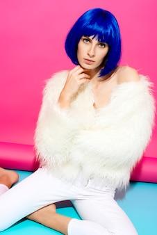 파란 가발에 매력적인 펑키 섹시한 여자와 분홍색과 분홍색 파란색 배경에 흰색 모피 코트