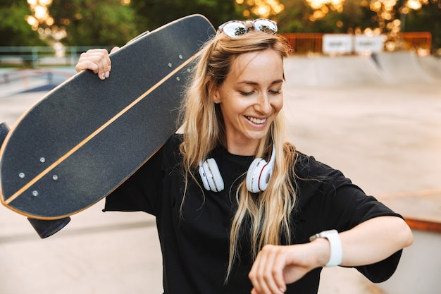 スケートパークを歩きながら、時間をチェックしながらロングボードを運ぶ魅力的なファンキーな10代の少女