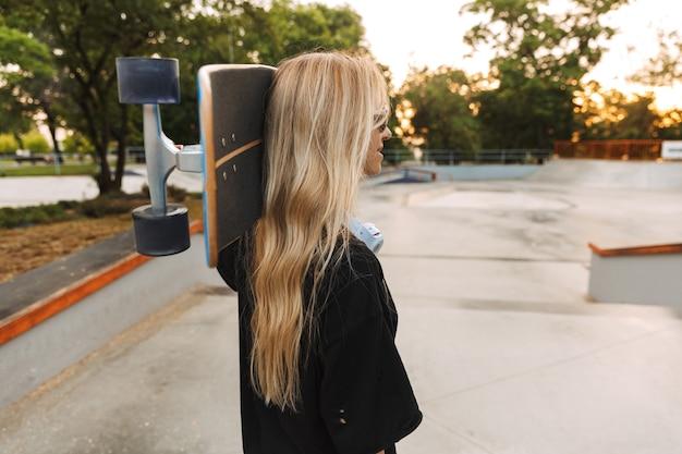 スケートパークを歩きながらロングボードを運ぶ魅力的なファンキーな10代の少女