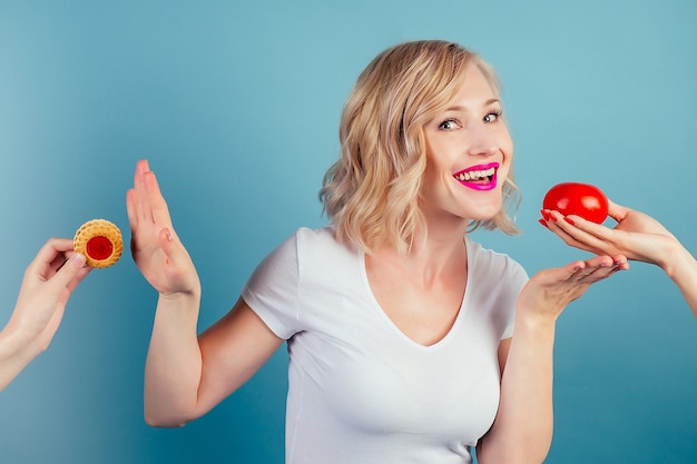 Привлекательная смешная блондинка делает выбор между высококалорийным печеньем и помидорами в студии на синем фоне. концепция здорового питания