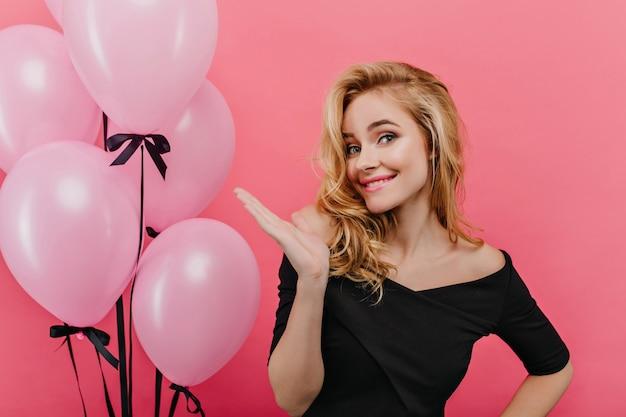 파티 촬영을 즐기는 금발 머리를 가진 매력적인 재미있는 소녀. 풍선 근처에 서 웃 고 검은 드레스에 관심이 여성 모델.